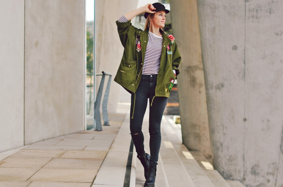 olive parka, flower patches, black pants, striped shirt