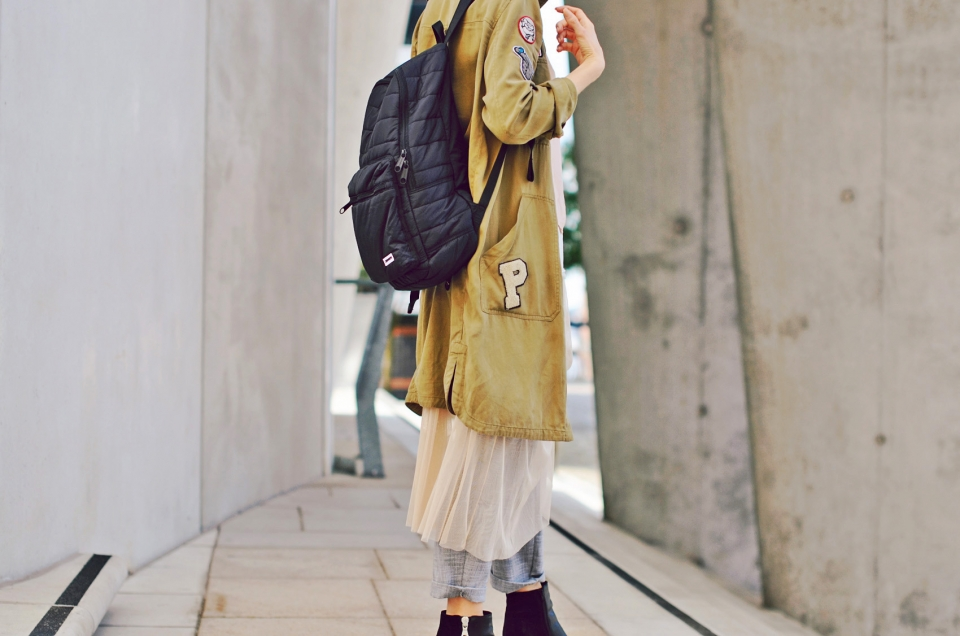 parka, patches, black rucksack, pleated-front trousers