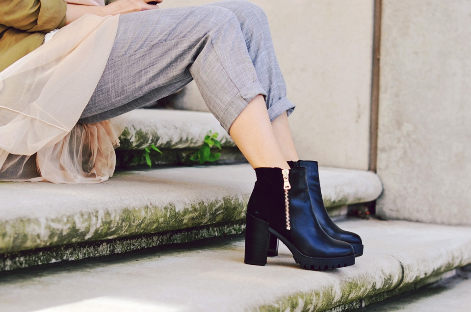 stairs, black boots, high heels, zipper details, grey pants